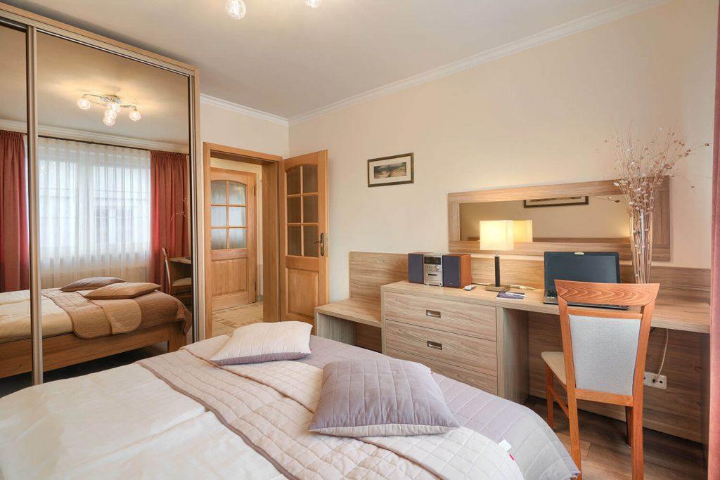 Apartament Alfa sypialnia z dużym podwójnym łóżkiem
